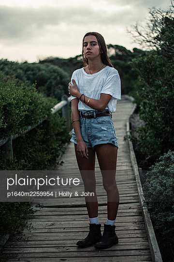 Young girl on wooden boardwalk - p1640m2259954 by Holly & John