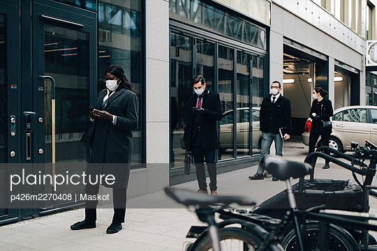 Business people maintaining social distancing while standing on footpath by building in city - p426m2270408 by Maskot