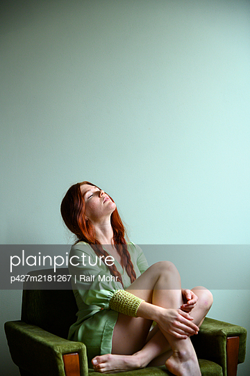 Red-haired woman on armchair - p427m2181267 by Ralf Mohr