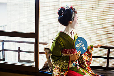 A woman dressed in the traditional geisha style, wearing a kimono and obi, with an elaborate hairstyle and floral hair clips, with white face makeup with bright red lips and dark eyes. Seated by a window with a fan. - p1100m1185712 by Mint Images