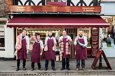 Group of men, butchers and fishmonger, wearing aprons, standing on the pavement outside a butcher shop, holding pieces of meat and fish, looking at camera. - p1100m1575653 by Mint Images
