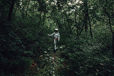 Spaceman exploring nature, looking at plants in forest - p300m2030488 by Vasily Pindyurin