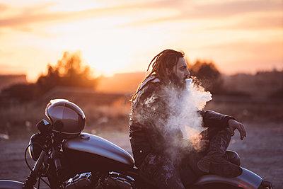 Bearded man with dreadlocks sitting on motorbike at sunset smoking electronic cigarette - p300m2104512 by Oscar Carrascosa Martinez