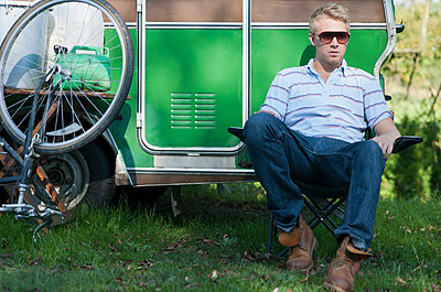 Man sitting outside trailer in park - p429m1450676 by Colin Hawkins