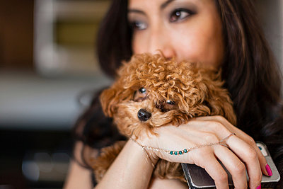 Portrait of mid adult female holding dog and smartphone - p924m805967f by Zave Smith