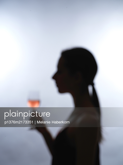 Silhouette of woman holding glass of wine - p1376m2173351 by Melanie Haberkorn