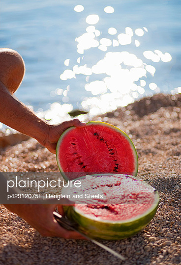 Man cutting watermelon at the beach - p42912075f by Henglein and Steets