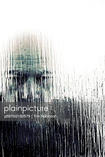 Man looking through textured glass window - p597m2182579 by Tim Robinson