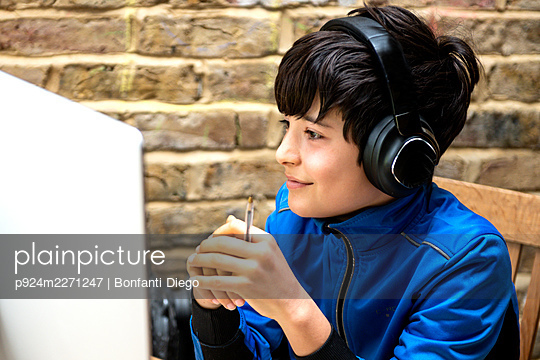 UK, Smiling boy (10-11) in headphones having on-line lesson - p924m2271247 by Bonfanti Diego