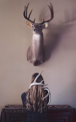 Woman Entrapped by Antlers Kneeling Under Mounted Deer Head  - p1617m2200367 by Barb McKinney