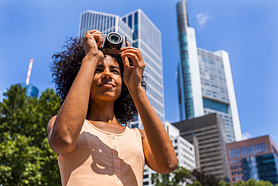 Germany, Frankfurt, portrait of young woman  taking photos in the city - p300m2030282 by Tom Chance