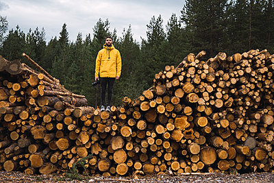 Man with camera standing on stack of wood - p300m2060840 by Kike Arnaiz