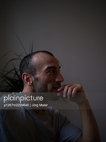 Musing young man in his apartment - p1267m2229640 by Wolf Meier