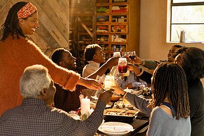 Multi-generation family enjoying Christmas dinner, toasting glasses - p1023m1575858 by Sam Edwards