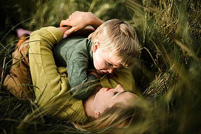 Mother hugs her little son outdoor - p1166m2095459 by Cavan Images