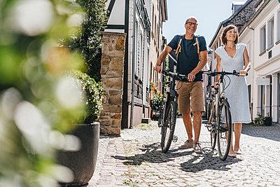 Mature couple pushing bikes through Old Town - p586m1171826 by Kniel Synnatzschke