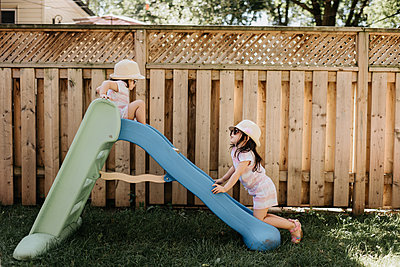 Sisters playing on slide in backyard   - p924m2153112 by Sara Monika