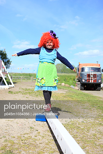 Clownin balanciert auf Holzbalken - p045m1034356 von Jasmin Sander