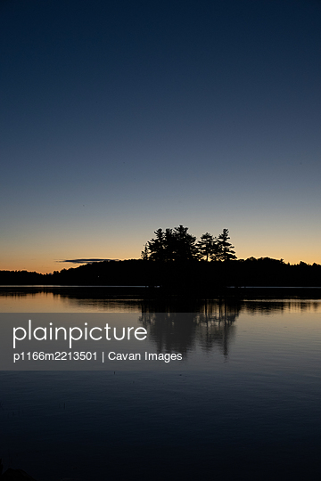 Silhouette of trees on an island in a lake in Ontario at sunrise. - p1166m2213501 by Cavan Images