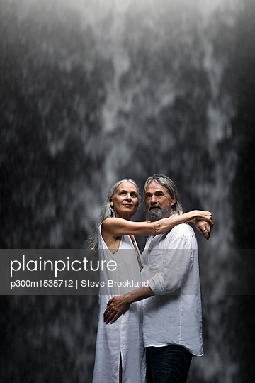 Handsome senior couple hugging in front of tropical waterfall - p300m1535712 by Steve Brookland