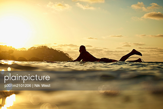 Male surfer laying on surfboard on sunny ocean at sunset, Sayulita, Nayarit, Mexico - p301m2101206 by Nik West