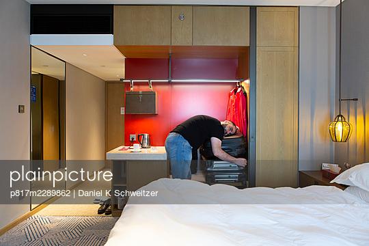Man with full beard resting head on suitcase - p817m2289862 by Daniel K Schweitzer