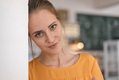 Young woman standing in cafe, portrait - p300m2024218 von Joseffson