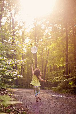 Girl playing with butterfly net in forest - p555m1409489 by Shestock