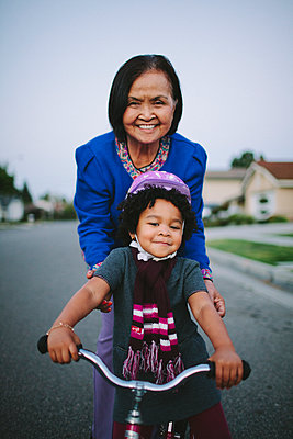 Grandmother teaching granddaughter to ride bicycle on suburban street - p555m1409613 by Shestock