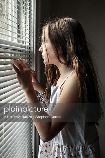 Mädchen blickt durch die Jalousie am Fenster - p1019m2134679 von Stephen Carroll