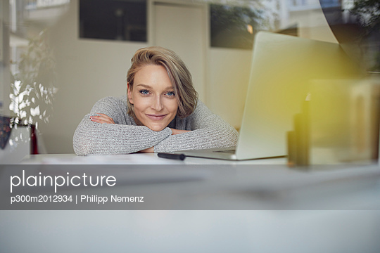 Portrait of smiling young woman leaning on desk with laptop - p300m2012934 von Philipp Nemenz