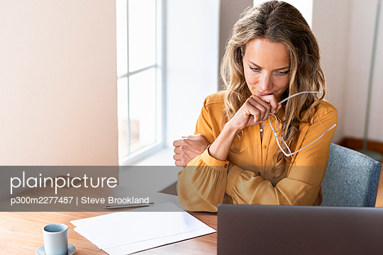 Female professional holding eyeglasses while looking at laptop on desk - p300m2277487 by Steve Brookland