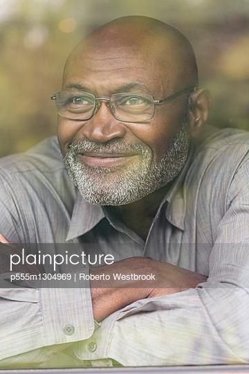 Smiling Black man behind window - p555m1304969 by Roberto Westbrook