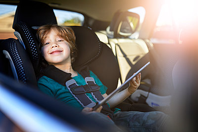 Portrait of smiling boy using digital tablet while sitting at back seat in car - p1166m2201297 by Cavan Images