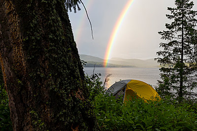 Tent in bushes near trees on shore with vivid rainbow over calm lake - p1166m2212355 by Cavan Images