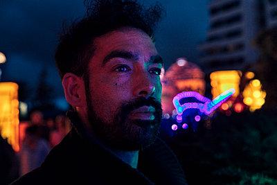 Hipster Mann schaut in bunt beleuchtetem Park in die Ferne - p1491m1582683 von Jessica Prautzsch