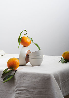 Oranges and dishes on a table - p1629m2211340 by martinameier