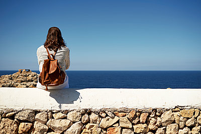 Young brunette woman sitting on wall, looking at view - p300m2029255 by Ivan Gener