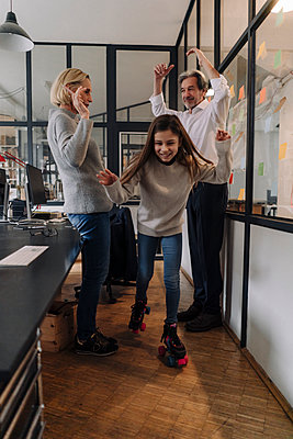 Businessman and businesswoman with girl on roller skates in office - p300m2154918 by Gustafsson
