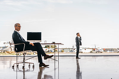 Mature businessman at desk on airport - p586m1208543 by Kniel Synnatzschke