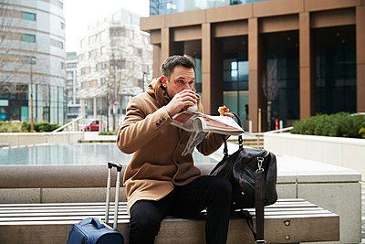 UK, London, Man eating breakfast on bench - p924m2271288 by Peter Muller
