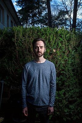 Junger Mann mit Vollbart vor einer Hecke - p975m2172252 von Hayden Verry