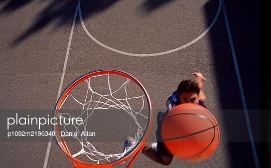 Sportler wirft wirft Basketball in den Korb - p1082m2196348 von Daniel Allan