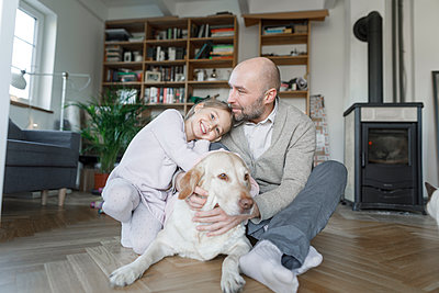 Portrait of father sitting with his little daughter and the dog on the floor at home - p300m2167207 by Katharina Mikhrin