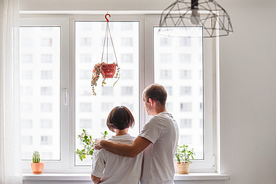 Husband and wife embracing while looking through window at home - p300m2276722 by Katharina und Ekaterina
