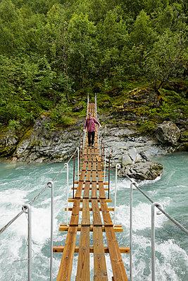 Norway, Jotunheimen, Utladalen, Man walking on suspension bridge over river - p352m1349393 by Gustaf Emanuelsson