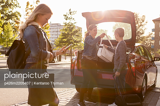 Side view of teenager using phone while mother and son keeping bag in car trunk - p426m2205407 by Kentaroo Tryman