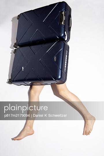 Naked man hiding behind trolleybag - p817m2179094 by Daniel K Schweitzer