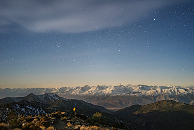 Distant view of hiker standing amidst mountains against star field sky - p1166m1473846 by Cavan Images