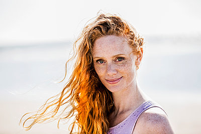 Portrait of smiling redheaded woman outdoors - p300m2024140 by Jo Kirchherr